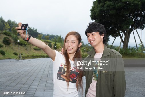 Young man and woman photographing themselves with camera phone : Foto de stock