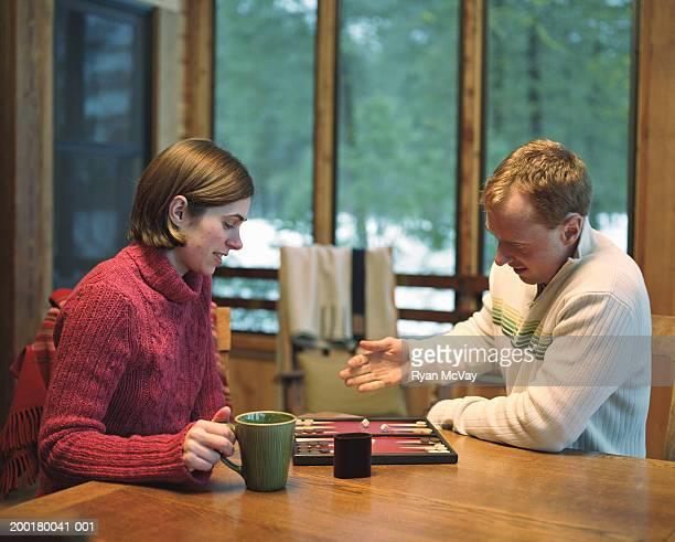 Junger Mann und Frau spielt backgammon, Seitenansicht