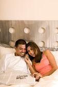Young man and woman reading newspaper and using cell phone in bed