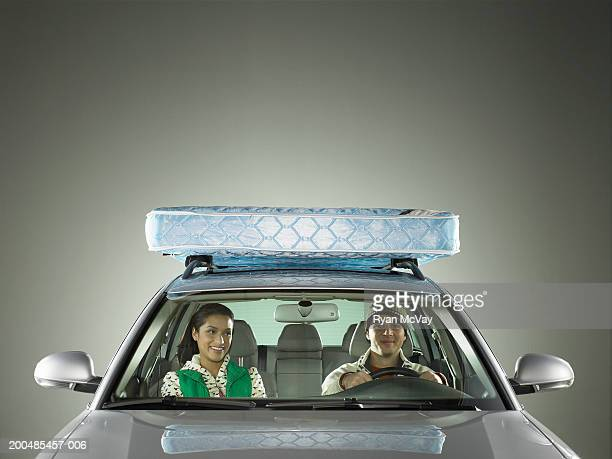Young man and woman riding in car with mattress strapped to roof