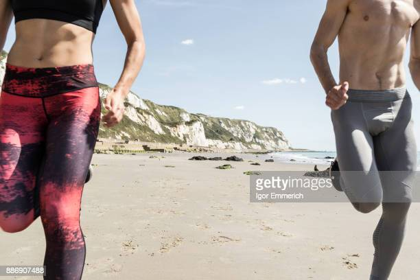 Young man and woman running along beach, mid section