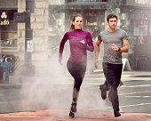 Young man and woman running through steam, Pioneer Square, Seattle, USA