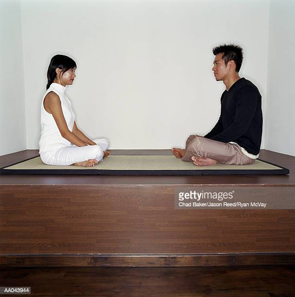 Young man and woman sitting across from each other on mat, profile