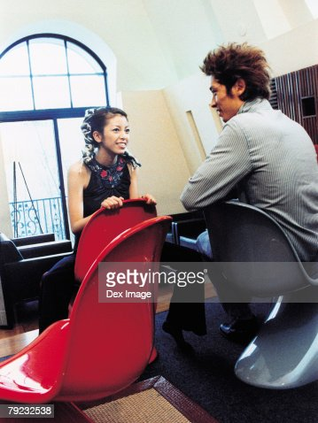 Young man and woman sitting across from each other, talking : Stock Photo