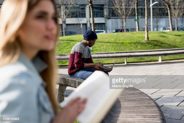 Young man and woman sitting apart on bench, man using laptop, woman holding book