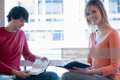 Young man and woman sitting at window reading, smiling