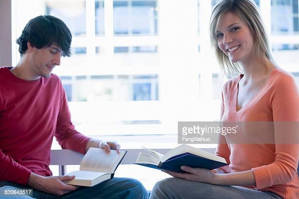 Jeune homme et une femme assis à la fenêtre de lecture, souriant