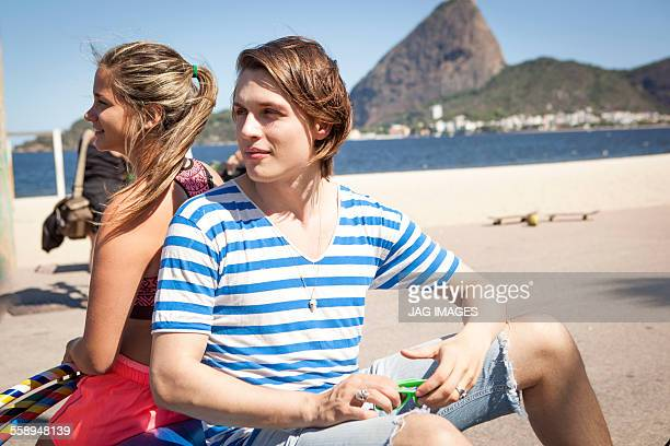 Young man and woman sitting back to back, outdoors