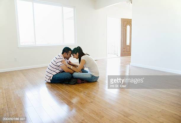 Young man and woman sitting head to head on floor in empty living room