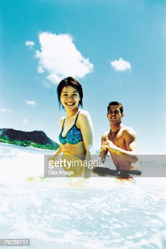 Young man and woman sitting on surfboard in water : Stock Photo