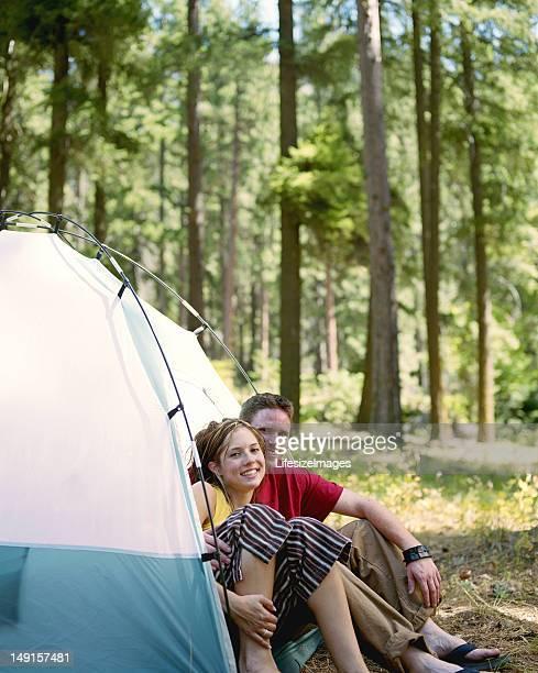 Jeune homme et une femme assis ensemble dans une tente, portrait