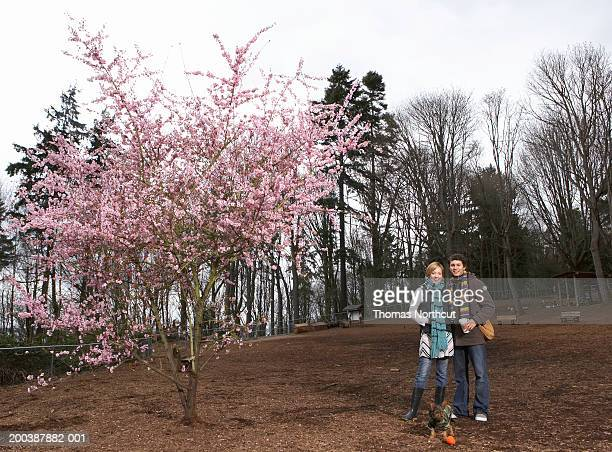 Young man and woman standing beside dog in dog park, spring