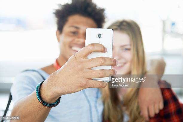 young man and woman taking selfie with smart phone