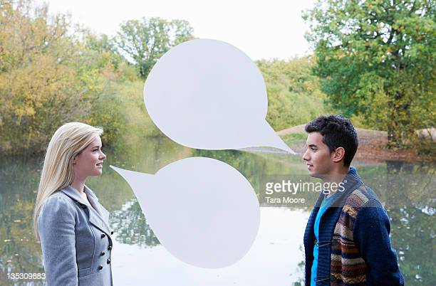 young man and woman talking with speech bubbles