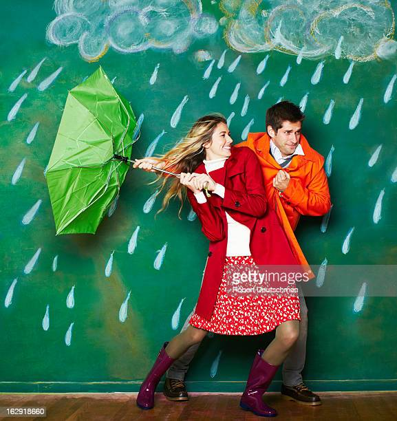 A young man and woman trudging through the rain.