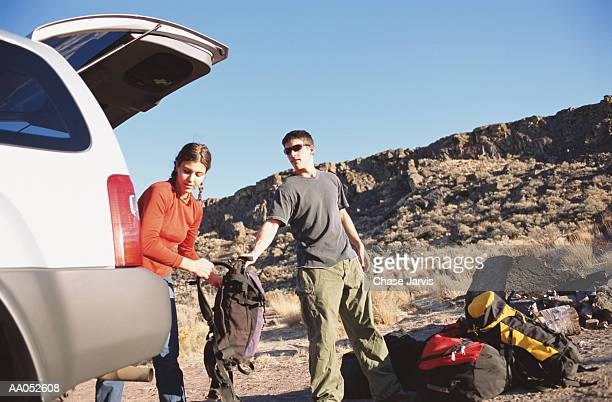 Young man and woman unloading camping gear from vehicle at campsite