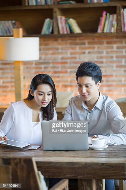 Young man and woman using laptop in cafe