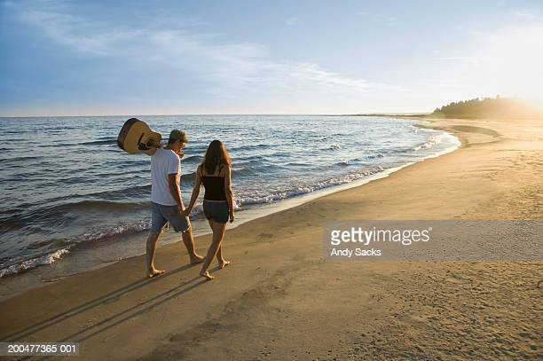 Young man and woman walk along beach, sunset, rear view