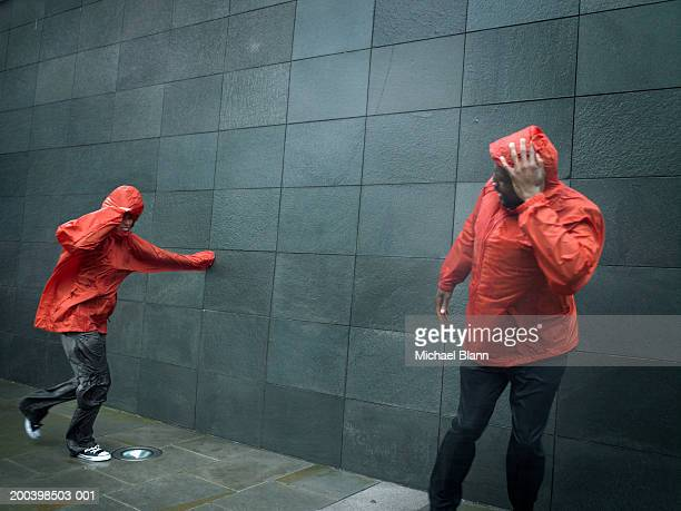 Young man and woman wearing anoraks, struggling against wind