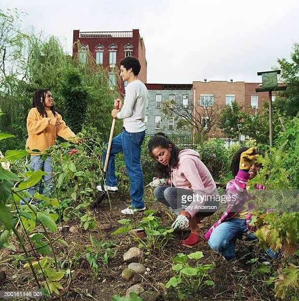 Young man and woman with kids (7-10) working in garden