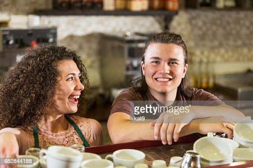 Young man and woman working in coffee shop : ストックフォト
