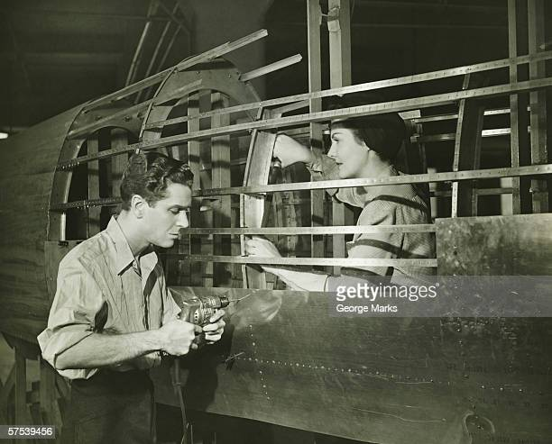 Young man and woman working in plane body in factory, (B&W)