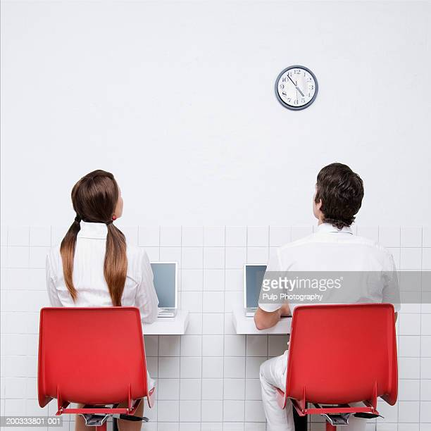 Young man and woman working on laptops, looking at clock, rear view