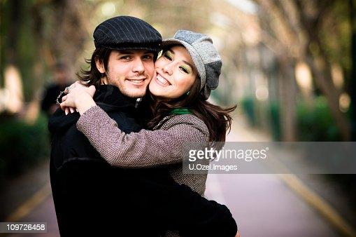 A young man and women hugging each other affectionately : Bildbanksbilder