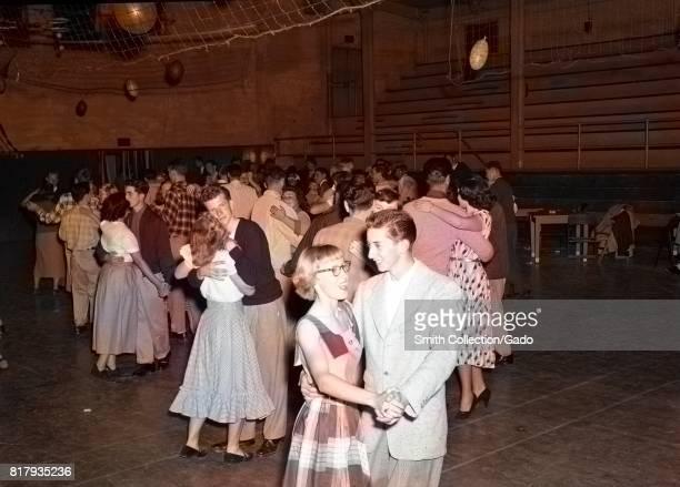 A young man and young woman hold hands and laugh together while slow dancing during a high school dance in the gymnasium at Monterey Union High...