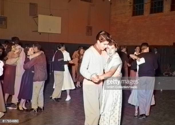 A young man and young woman hold hands while slow dancing during a high school dance in the gymnasium at Monterey Union High School while other...