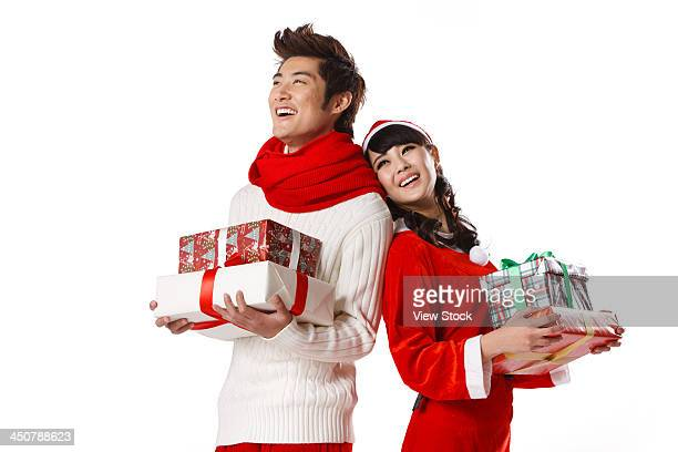 Young man and young woman holding Christmas gift