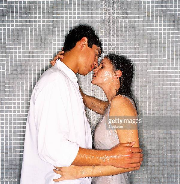 Young man and young woman kissing under a shower