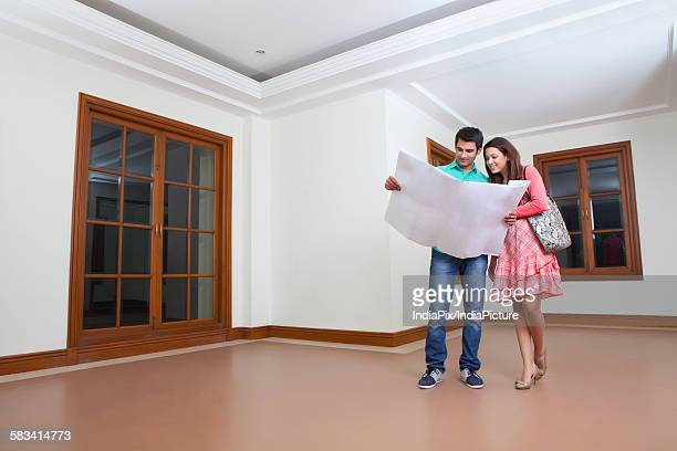 Young man and young woman looking at lay out of house