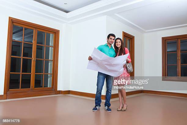 Young man and young woman looking at lay out of houseYoung man and young woman looking at lay out of house