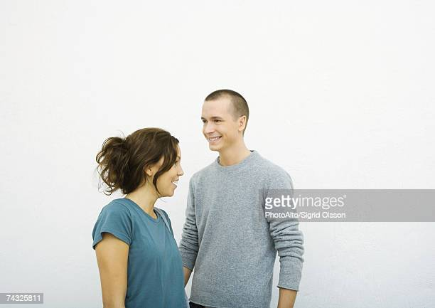 Young man and young woman standing together, looking in opposite directions, smiling