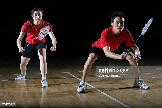 Young man and young woman, teammates, crouch in preparation for a game of badminton.