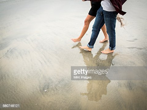 Young man and young woman walking on a beach.