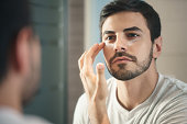 Young hispanic people and male beauty. Metrosexual man applying lotion for anti-aging treatment around eye