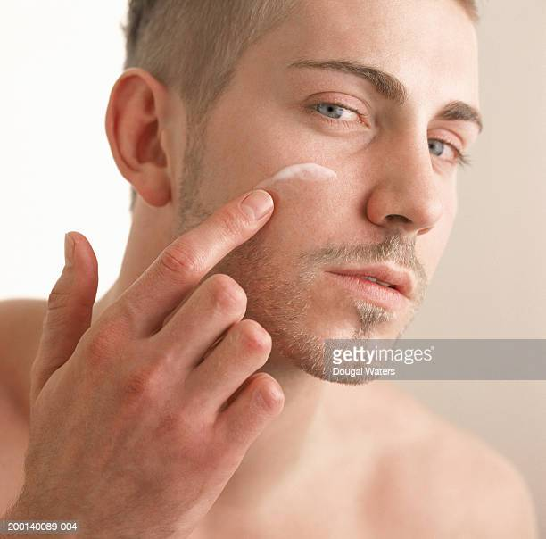 Young man applying cream to face, close-up