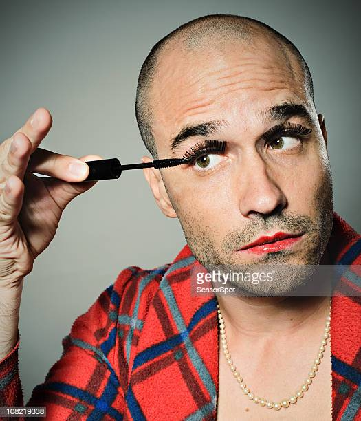 Young Man Applying False Eyelashes and Mascara