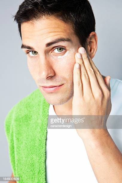 Young man applying moisturizing cream