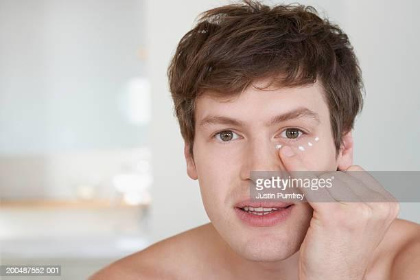 Young man applying mosituriser, portrait