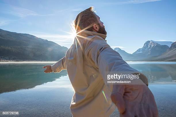 Jeune homme bras tendus par le lac au lever du soleil