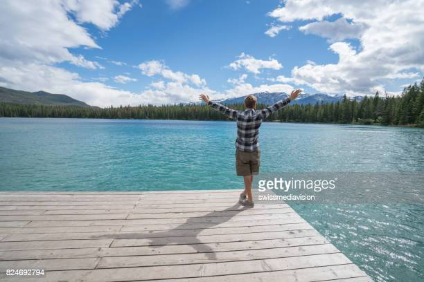 Young man arms outstretched  on lake pier