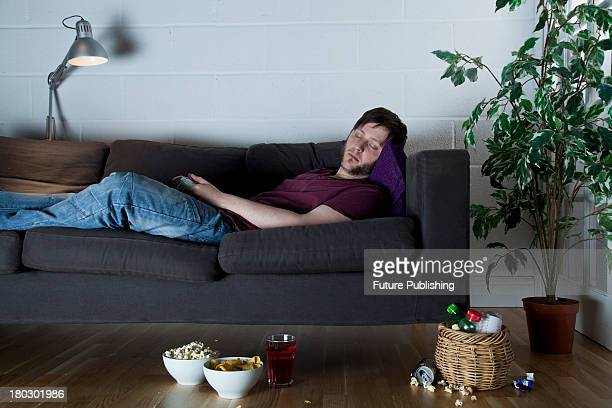 A young man asleep on a sofa with an XBox 360 wireless controller taken on July 9 2013