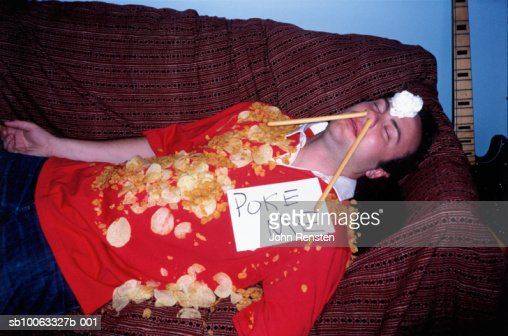 Young man asleep on sofa covered in crisps wearing sign
