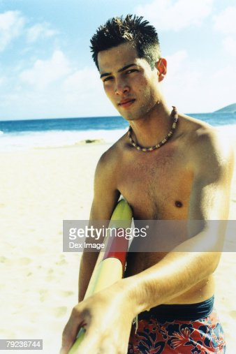 Young man at a beach, holding surfboard : Stock Photo
