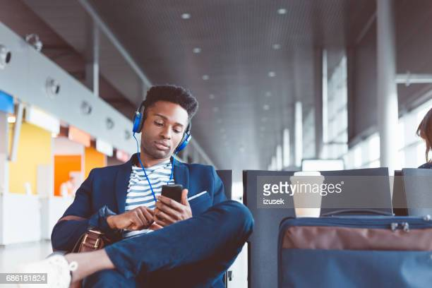 Young man at airport lounge listening music