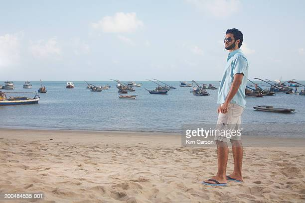 Young man at beach, jangadas in background