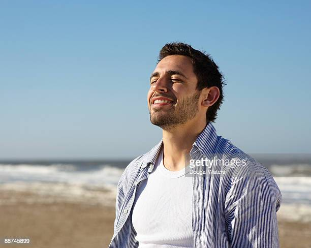 Young man at beach with eyes closed.